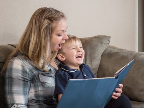 mother reading to and laughing with her son